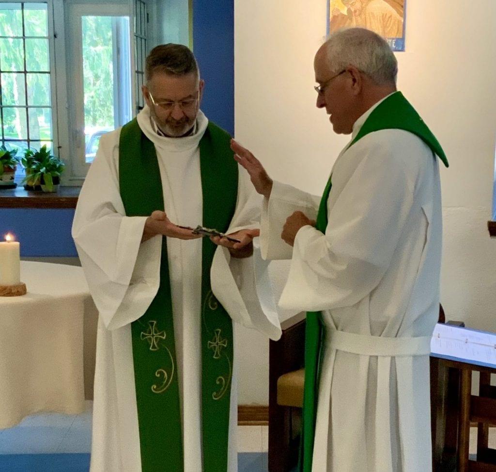 Fr. Gabriel Coté, SJ, and Fr. Erik Oland, SJ, hold the vow cross